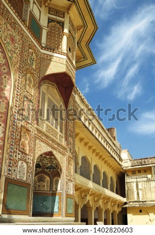 Part of the wall with paintings and carved balcony of the main palace in the ancient Amber fort. Jaipur, India.