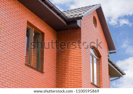 Part of wall made of the red brick, windows and fragment of roof of modern private dwelling house against of sky