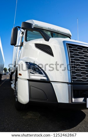 Part of white modern bonnet big rig semi truck with chrome grille and geometric shaped headlight standing in row on the truck stop and waiting for next cargo load for delivery #1252462867