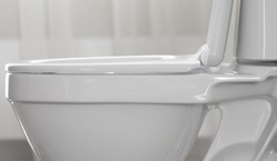 Part of white toilet bowl close-up.