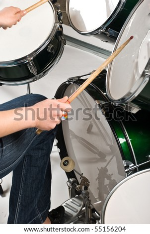 Part of woman  legs on drum pedal  holding drumsticks