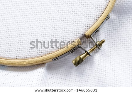 Part of wooden hoop with metal screw lock with blank white canvas on it