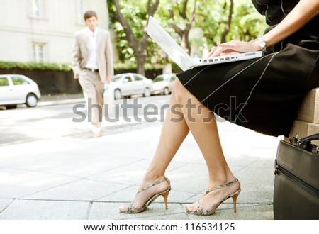 Part section of a young businesswoman working on her laptop computer while sitting in a classic street in the city with another businessman walking by.