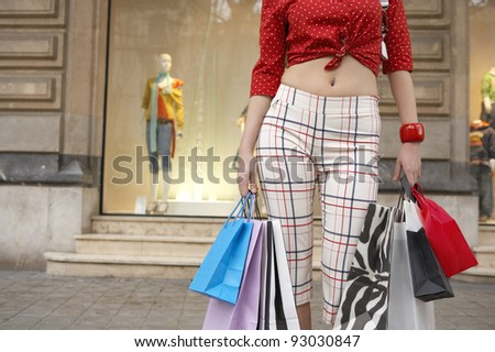 Part view of a young woman holding shopping bags in shopping street.