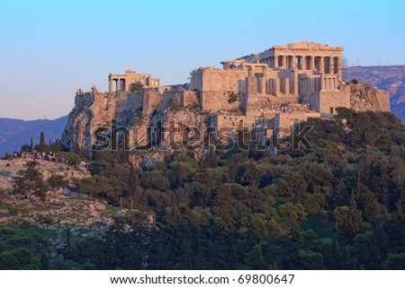 Parthenon on Acropolis hill in the afternoon with the national guard climbing the stairs to retrieve the flag