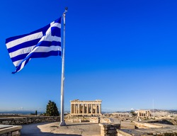 Parthenon temple on the Acropolis in Athens with Greek flag and blue sky, Greece