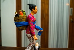 Partial and selective focus images the miniature of female traditional herbal drinks female seller. Suitable for decor and souvenirs.