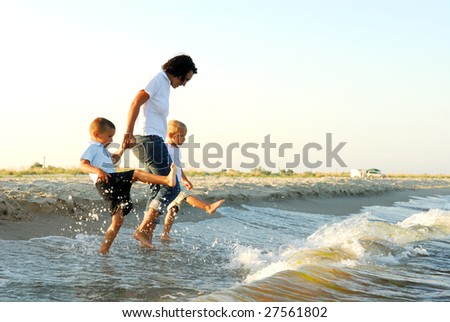 Partial profile of a woman holding the hands of two young boys, as they splash their feet in shallow water ahead of oncoming waves.