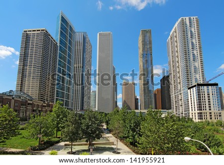 Partial skyline of skyscrapers near the Chicago River in the Loop area at the center of downtown Chicago, Illinois, against a bright blue sky.