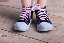 Partial success - child feet with two shoes tied together on wooden floor