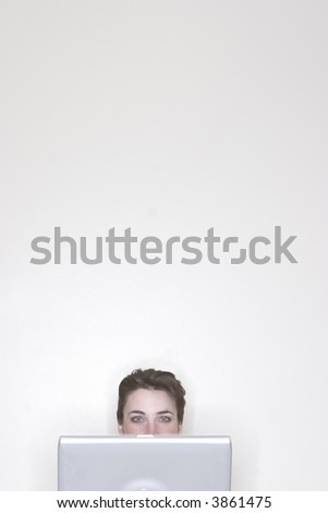 Partial view of a businesswoman as she is using her laptop in the office against a white background