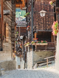 Partial view of beautiful traditional wooden houses, also called Swiss chalet, in a narrow alley in the alpine village of Grimentz, in the canton of Valais (Switzerland), municipality of Anniviers.
