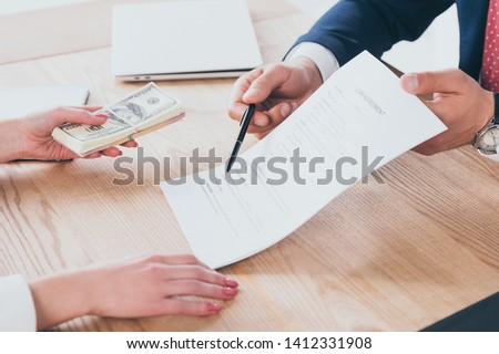 partial view of businessman pointing at signature place in loan agreement near woman holding dollar banknotes #1412331908