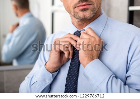 partial view of businessman tying necktie in bathroom