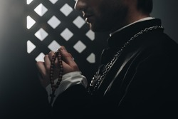 partial view of catholic priest holding wooden rosary beads near confessional grille in dark with rays of light