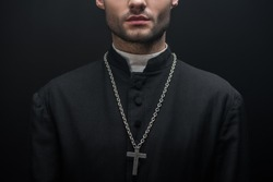 partial view of catholic priest with silver cross on necklace isolated on black