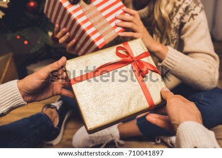 partial view of couple exchanging gifts while celebrating christmas together