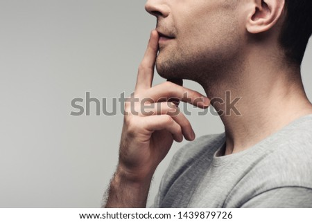 partial view of dumb man showing silence sign isolated on grey, human emotion and expression concept