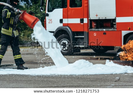 partial view of firefighter extinguishing fire with foam on street #1218271753