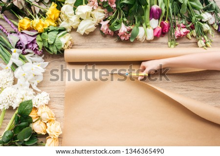 Partial view of florist cutting craft paper with scissors near flowers on wooden surface