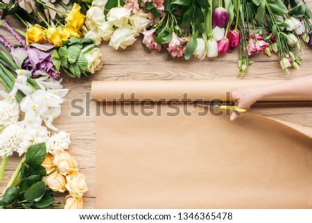 Partial view of florist cutting craft paper with scissors near flowers on wooden table