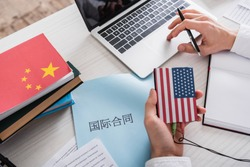 partial view of interpreter holding digital translator with usa flag emblem near paper with chinese hieroglyphs.Translation: 'international contract'