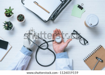 partial view of male doctor with prosthetic arm holding stethoscope