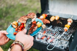 partial view of man wit tongs putting grilled food on plate during bbq in park