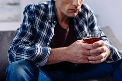 partial view of man with alcohol drink sitting on sofa at home