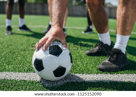 partial view of old player holding football ball with multiracial friends behind on football field