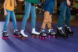 partial view of parents and kids skating on roller rink together