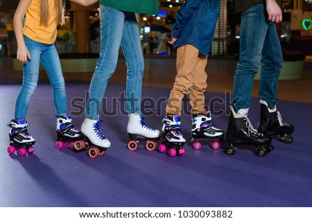 partial view of parents and kids skating on roller rink together - Shutterstock ID 1030093882