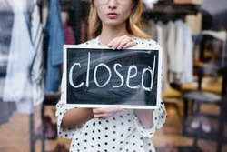 partial view of proprietor holding board with closed lettering in showroom, blurred background