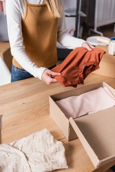 partial view of proprietor holding sweater near box with clothing in showroom
