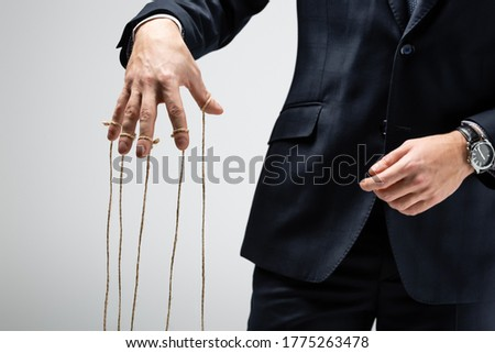 partial view of puppeteer in suit with strings on fingers isolated on grey Stockfoto ©