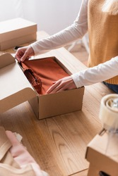 partial view of showroom proprietor packing sweater into box, blurred foreground