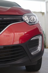 Partial view of the front grille and headlight of a ruby red car.