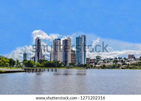 Partial view of the lake in the Parque das Nações Indígenas and buildings in the background, in the city of Campo Grande, capital of Mato Grosso do Sul, Brazil. City in the middle of nature. #1271202316
