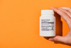 Partial view of woman holding white container with dietary supplements on orange background
