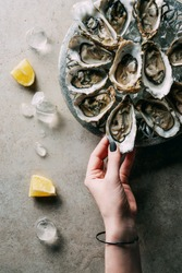 partial view of woman taking oyster from bowl on grey tabletop with ice and lemon pieces