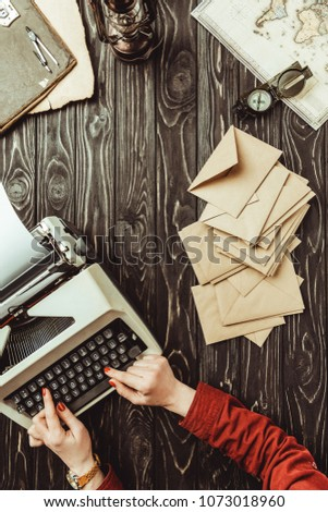 partial view of writer typing on typing typing machine with blank envelopes on wooden tabletop #1073018960
