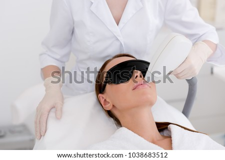 partial view of young woman receiving laser hair removal epilation on face in salon Foto stock ©