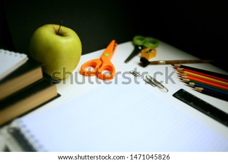 Partially blurred desktop photo. Back to school. Paper and notebook, compass, ruler, scissors, Apple, books, textbooks, workbooks, Desk, Board, sharpener and other stationery accessories for study.