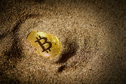 Partially Buried Bitcoin on sand with a vignette light.