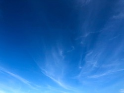 Partially cloudy. Hazy sky view. Pure white splash cloud against bright blue sky. Summer sky atmosphere. Moment of natural breathing climate scenery.