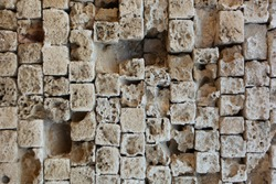 Partially destroyed masonry wall of old stone blocks of limestone. Background texture of weathered ancient brick wall. Gaps from broken stones