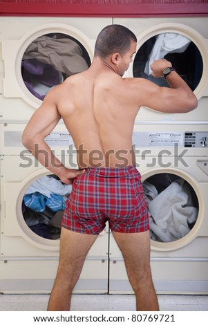 Partially dressed man in Laundromat checks the time