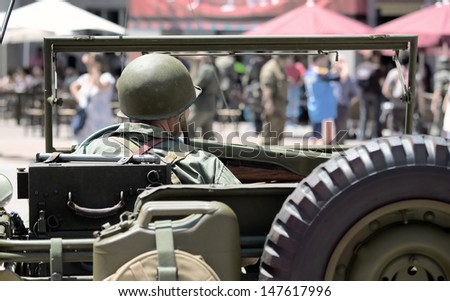 Participant uniform ww2 American soldier driving a car of the era in a recreation of World War two - stock photo