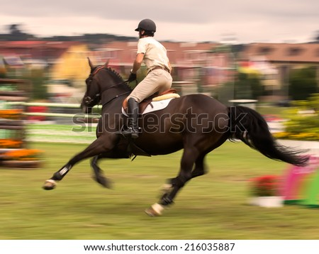 Participants in an international horse jumping competition, blur