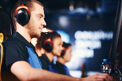 Participating in eSport tournament. Side view of fully concentrated caucasian guy, male cybersport gamer wearing headphones playing online video games